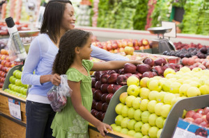 mome and daughter shopping for fruit in a grocery store