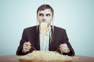 man binging on spaghetti