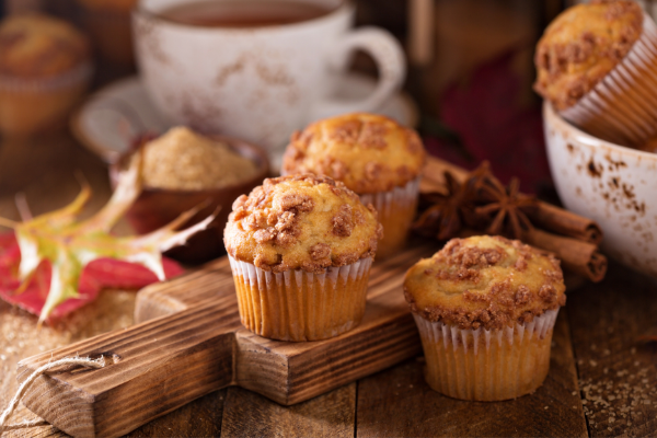 a display of rhubarb muffins on a wodden cutting board with a cup of coffee in a red and white mug in the background