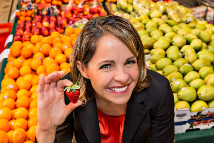 Andrea Holwegner holding a strawberry at the Farmer's Market