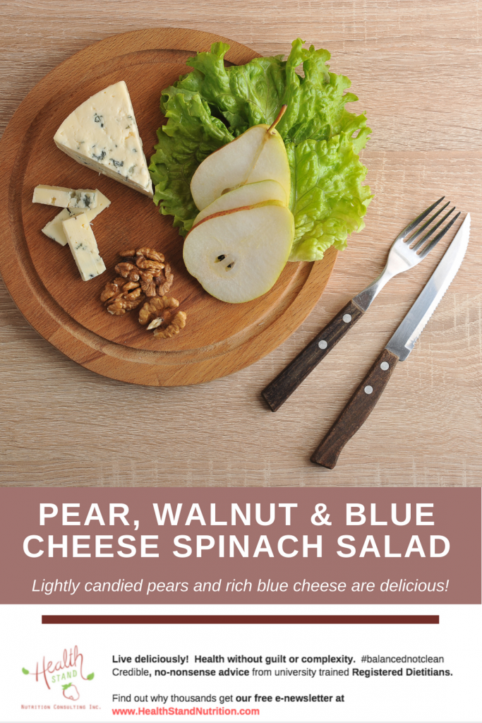 a round wooden board holds pear halves a blue cheese wedge and walnuts garnished with greens