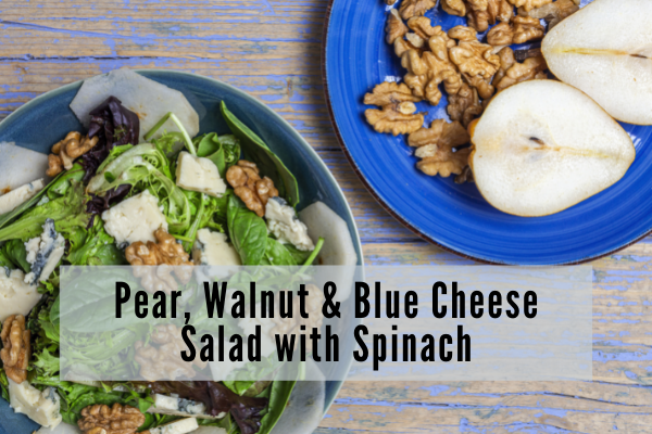 a pear walnut blue cheese and spinach salad sits to the left of a blue plate with a sliced pear and walnut halves on it