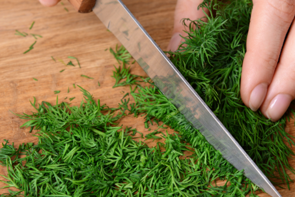 dill being chopped on a wooden cutting board