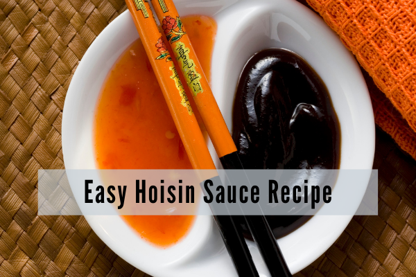 a yin yang shaped bowl with sweet chili sauce on one side and hoisin on the other. A pair of orange chopsticks with black handles the same color scheme as the sauces lay over the white bowl
