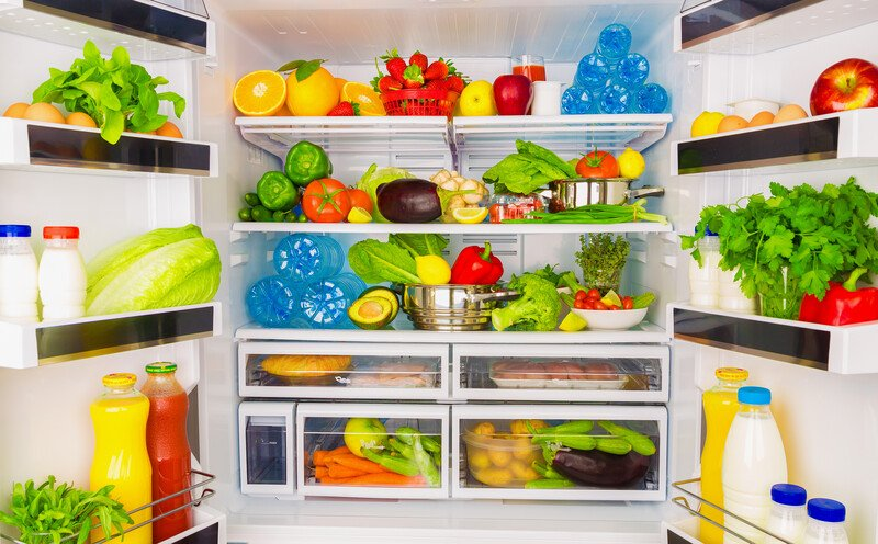 An open fridge overflowing with fresh fruits and vegetables
