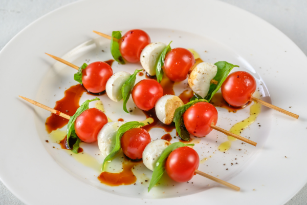 three skewers with cherry tomatoes, basil leaves and mozzarella cheese laid on a plate drizzled with olive oil and balsamic vinegar