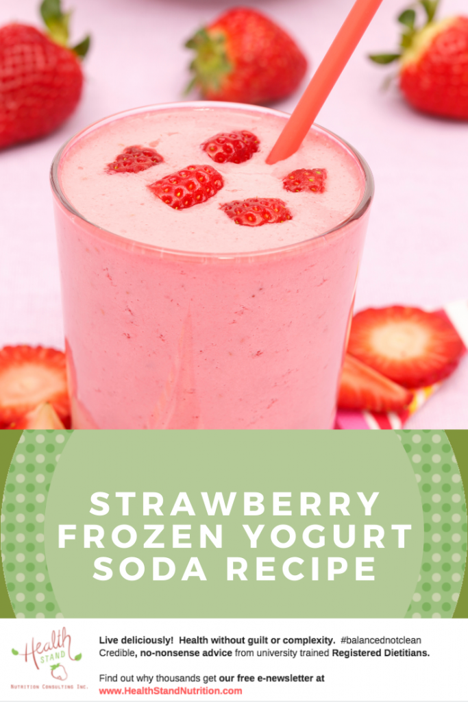 a creamy pale pink smoothie drink in a clear glass garnished with strrawberry pieces