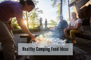 three people sitting around a camp fire by a lake while one person cooks
