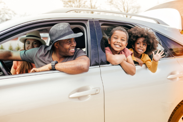 An african american family in a white car with the windows rolled down lean out the window for a picture - the dad in the drivers seat and two kids in teh back