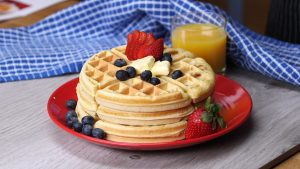stack of five waffles with strawberries, blueberries and whipped cream