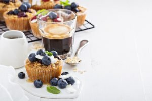 muffin topped with fresh blueberries and a glass of black espresso