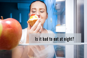 woman standing at refrigerator eating a pastry