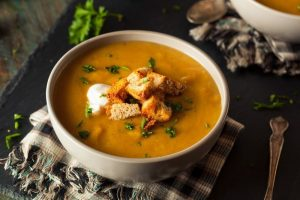 White bowl filled with yellow squash soup and croutons