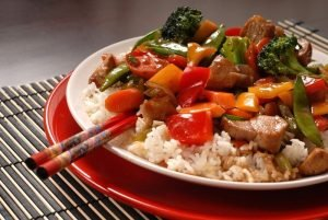 red plate of stir fry vegetables over white rice with chopsticks