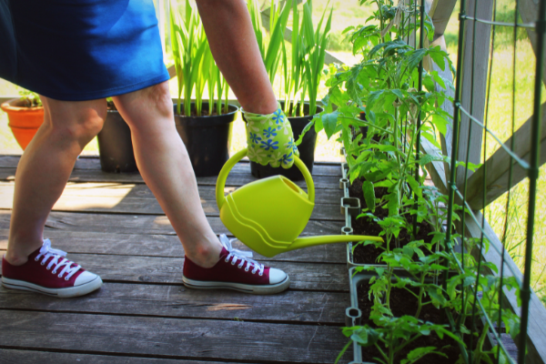 a woman in jean shorts and black sneakers waters plants on a balcony with a green watering can