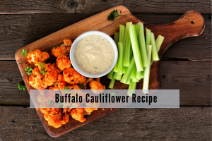 buffalo sauced cauliflower nuggets with ranch dip and celery on a wooden tray