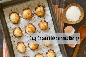 Sheet pan full of coconut macaroon cookies fresh out of the oven with an empty egg shell and bowl of sugar on the side