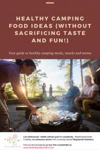 three people sitting around a campfire, one is cooking
