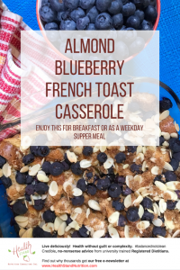 french toast casserole topped with blueberries and slivered almonds with a dish of blueberries beside it