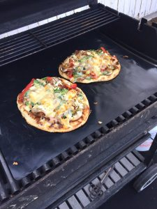 pizza being cooked on the grill