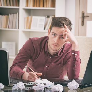 Man in burgundy dress shirt looking frustrated surrounded by wadded up sheets of paper