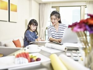 Woman in striped shirt working at laptop while helping her young daughter standing beside her