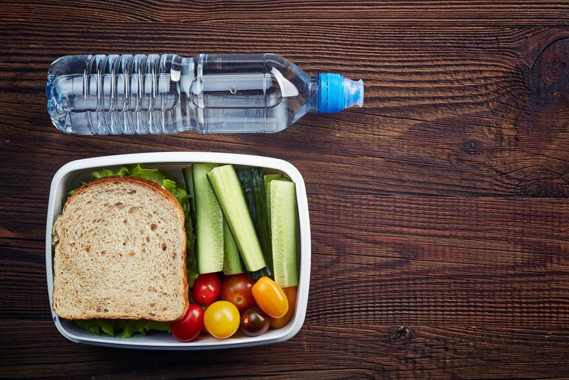 lunch box with sandwich on wheat bread, celery sticks, cherry tomatoes and a bottle of water