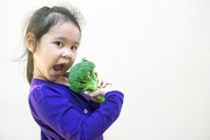Young girl in a blue dress eating a large piece of raw broccoli