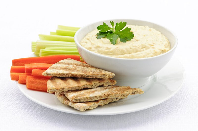 white plate with toasted pita, raw peppers and cucmbers and a bowl of hummus for dipping