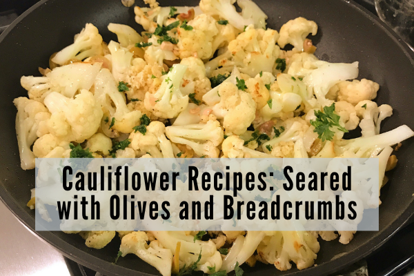 cauliflower seared in a skillet garnished with olives