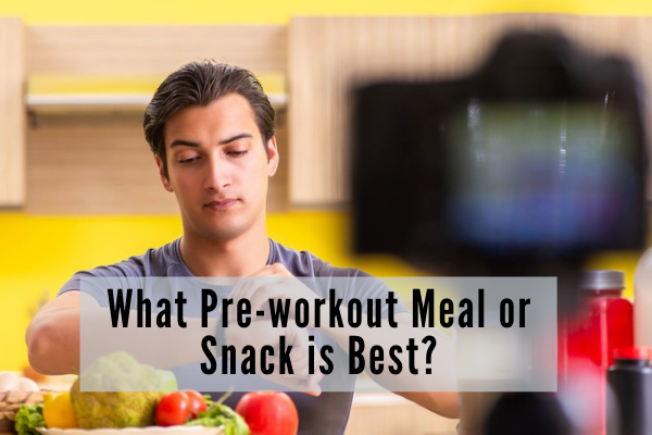 Fit man in grey tshirt checking his watch while a number of healthy foods are displayed in front of him.