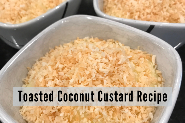 bowl of coconut custard topped with golden brown toasted coconut