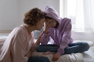 mom kneeling beside a teenager in a hoodie sitting on their bed having a seriousl conversation