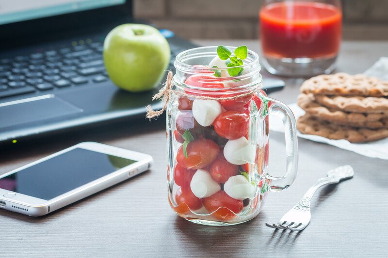 Desk with a mason jar boconccini salad of cherry tomatoes and mozzarella balls and a green apple on teh side