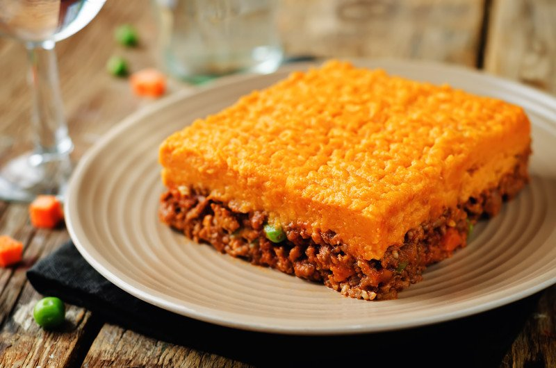Ground beef mixed with vegetables in a brown sauce topped with mashed sweet potato served on a white plate