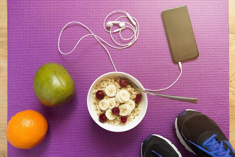 A purple yoga mat with running shoes, a personal music payer, a bowl of oats topped with bannans and berries, and apple and an orange arranged on it