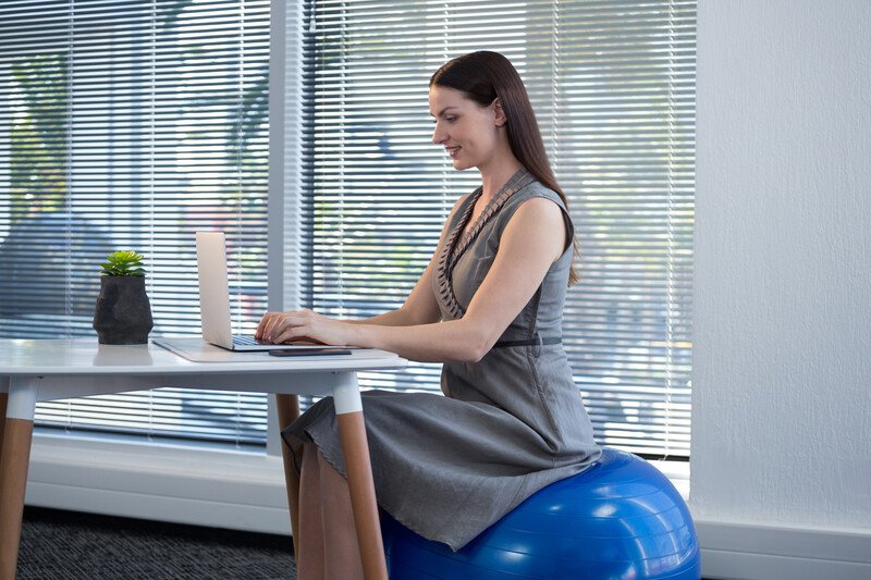 Woman sitting on a blue yoga ball working at her laptop in front of a large window