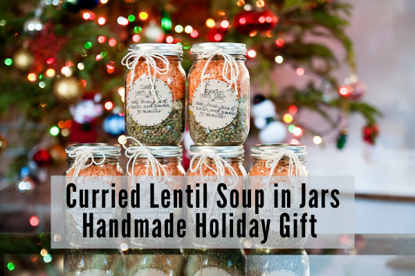 a tower of green and red lentil soup mix in clear mason jars with handmade labels in front of a christmas tree