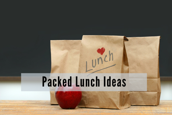 Three paper lunch bags on a desk along with a red apple. One bag has lunch and a red heart printed on it.
