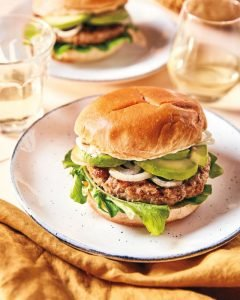 Turkey burger topped with pickles onions and lettuce on a soft white bun