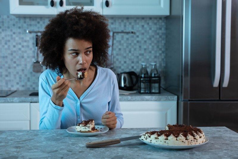 woman wearing pajamas sitting at a kitchen counter eating a slice of pie