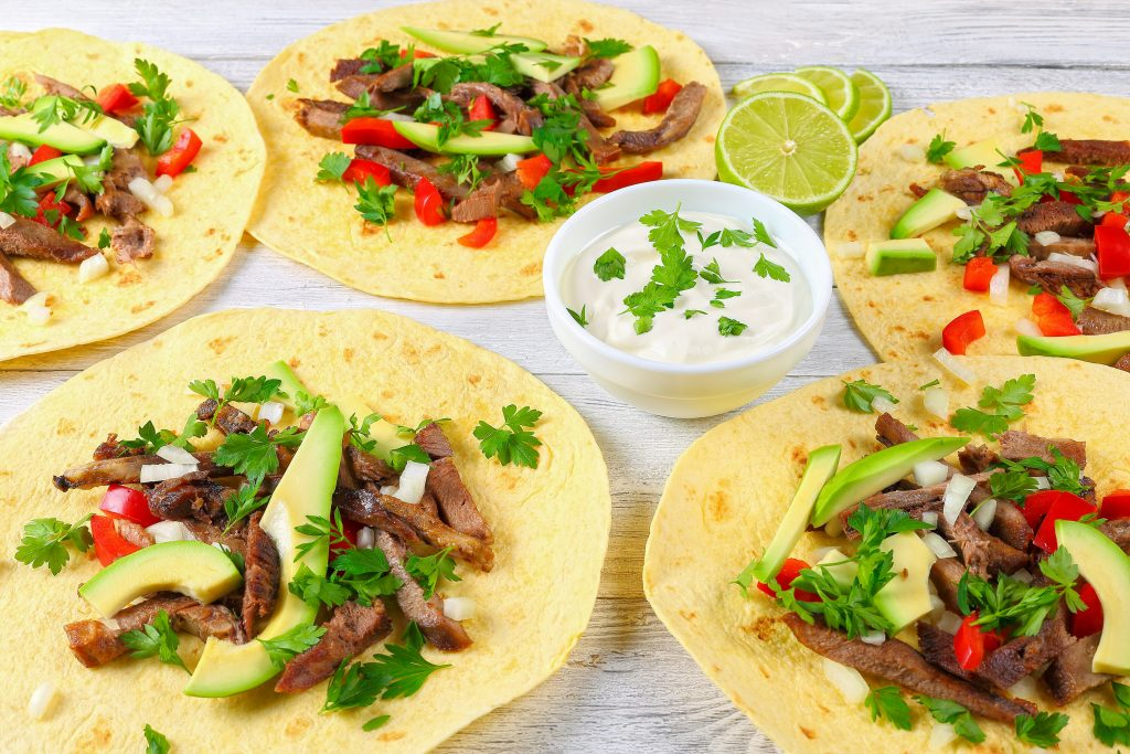 four flour tortillas topped with meat, greens and avocado with a bowl of sour cream in the center