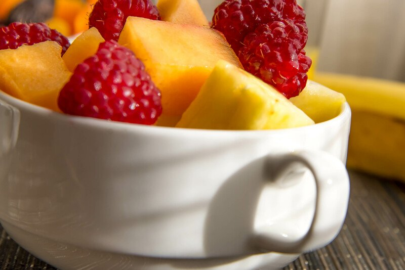 a mug filed with sliced strawberries, pineapple and cantelope pieces
