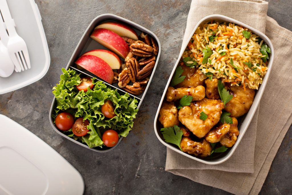 bento lunch container with salad on one side and apples and pecan on the other. Another bento contains grilled chicken and rice.