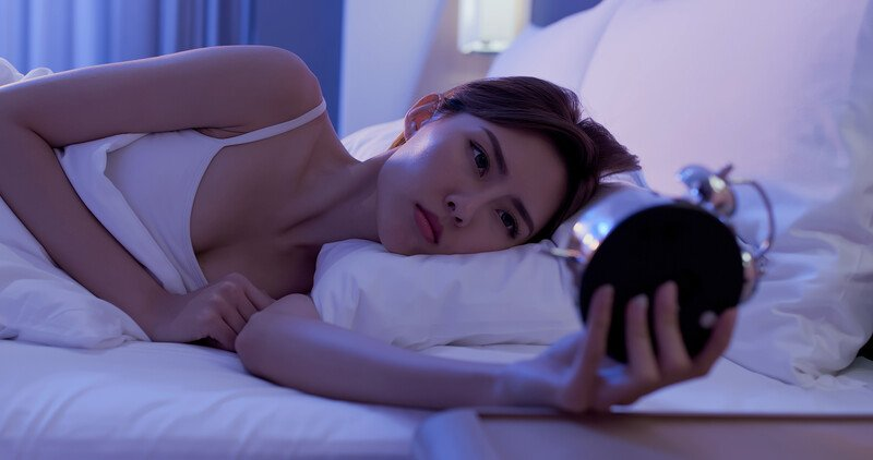 young woman lying in bed holding her alarm clock in one hand