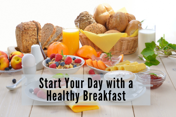 a full breakfast spread with bread, pastries, fruit, yogurt, ham and coffee