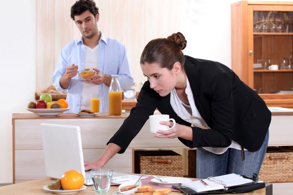 A woman drinking coffee and standing in front of her laptop while her partner eats cereal in teh background