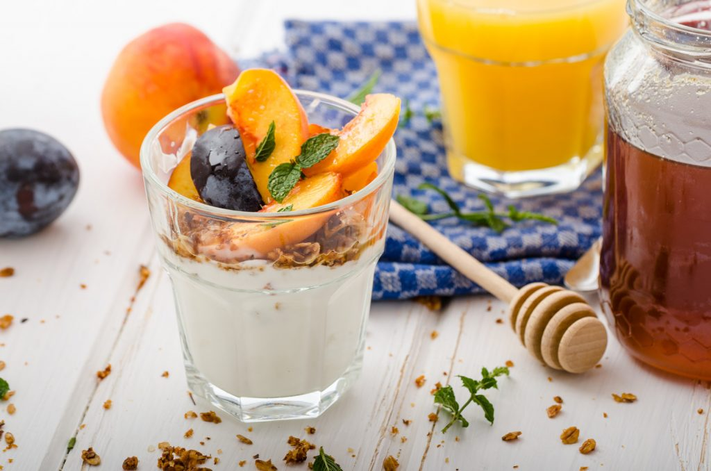 Yogurt parfait in a glass cup along with a glass of orange juice