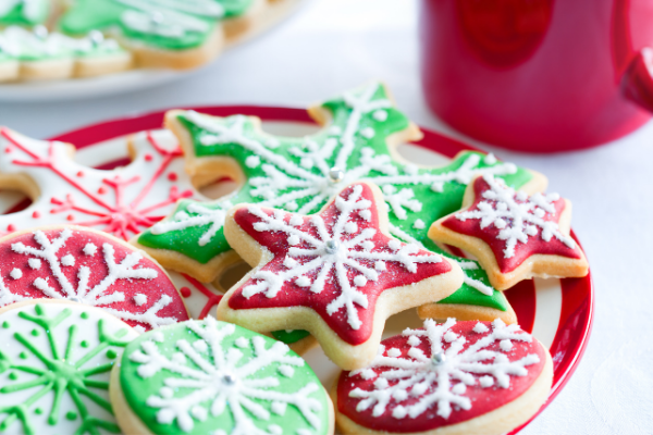 Star shaped sugar cookies frosted in red and green with white snowfakes drawn on them