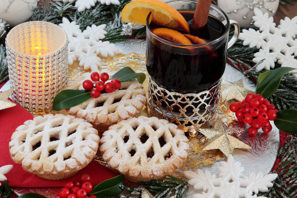Small mince pies and a glass of hot mulled wine garnished with orange slices on a festive table setting